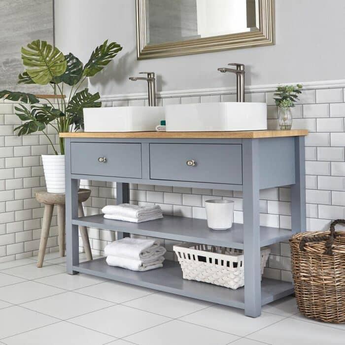 Lavabo sobre encimera con mueble en color gris claro.
