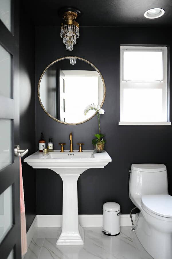 Paredes negras con accesorios de baño blanco.